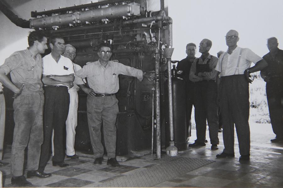 Directivos junto a personal de la Sección Redes de la Cooperativa, frente a uno de los motores. Año 1966